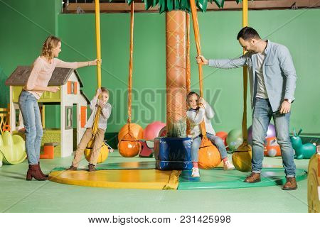Smiling Parents Looking At Cute Happy Children Swinging On Swings In Game Center