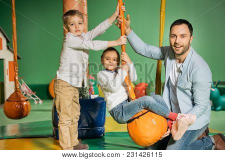 Happy Father With Adorable Kids Smiling At Camera While Playing In Entertainment Center