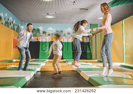 Happy Family Playing And Jumping Together In Entertainment Center