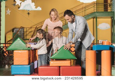 Happy Parents With Adorable Little Kids Playing Together With Colorful Blocks In Game Center