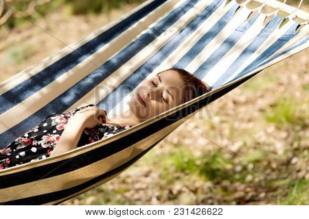 Woman relaxing in the hammock, hot sunny day