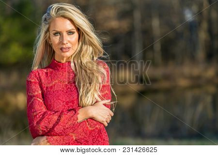 A beautiful blonde model posing in an outdoor environment