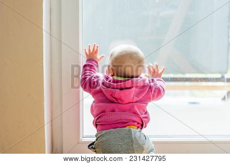 Baby Girl Looking Through Balcony. Leaning On Glass And Exploring.