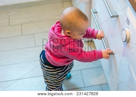 Baby Exploring Kitchen. Protected Drawers To Provide Safety.