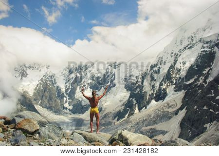 Athletic Man Stands At Great Height In Front Of The Huge Mountains And Welcomes Them. Victory And Fr