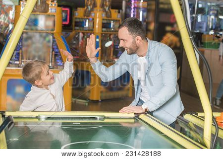 Happy Father And Son Giving High Five While Playing Air Hockey In Entertainment Center