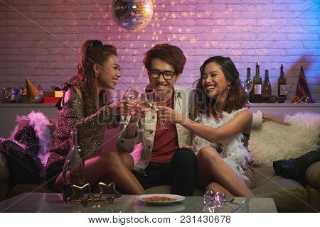 Celebrating New Year Eve With Friends: Joyful Asian Women And Man Sitting On Cozy Sofa At Night Club