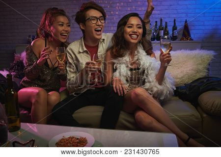 Attractive Young Women And Their Handsome Friend Sitting On Cozy Sofa With Champagne Flutes In Hands