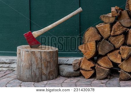Close Up Of Fire Wood And Axe On Cabin Patio