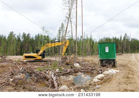 Excavator And Cabins For Forestry Workers On A Forest Felling Plot. Wood Industry In Russia