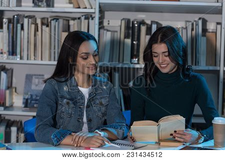Two Multicultural Female Friends Looking At Book In Library