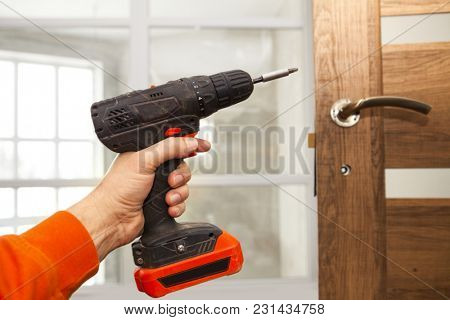 The screw gun in a hand of the master who establishes a door