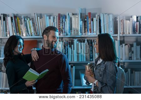 Happy Multicultural Students With Books In Library