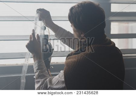 A Man In A White Shirt And A Brown Sweater - A Photographer, Examines The Film In The Light, Vitang