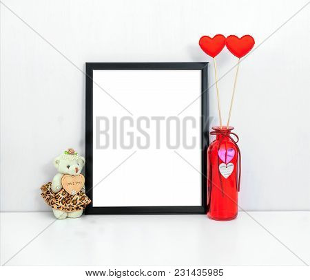 8x10 Thin Black Frame Mockup With A Red Vase And Toy. Portrait Orientation.