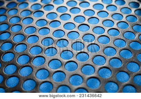 Black Metal Computer Case Panel Mesh With Holes On Blue Background. Abstract Close Up Image