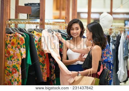Pretty Asian Young Women Shopping For Dresses In Mall