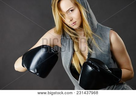 Young Hooded Woman Fighting Boxing. Blonde Attractive Girl Wearing Black Punch Gloves. Sport And Fit