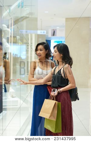 Excited Young Vietnamese Women Looking At Something In Shop Window