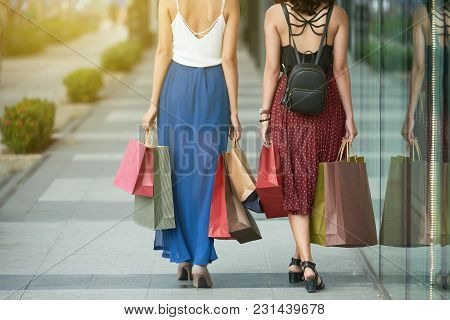 Rear View Two Young Women With Shopping Bags Walking Outdoors