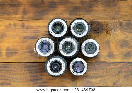 Several Photographic Lenses Lie On A Brown Wooden Background. Space For Text