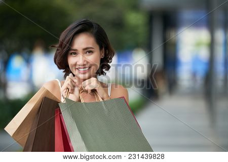 Portrait Of Attractive Young Asian Woman Holding Shopping Bags