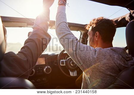 Young adult friends in a car looking out of open windows