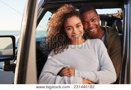 Young mixed race couple embracing by car, close up