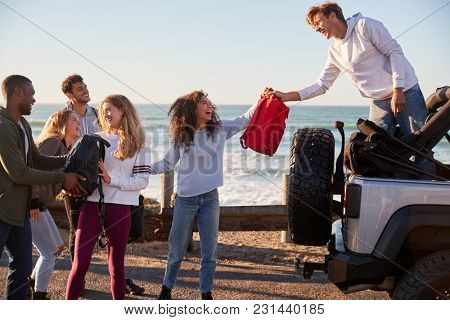 Young adult friends unloading backpacks from the back of car