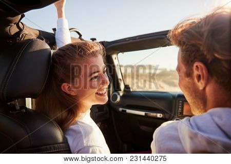 Happy couple drive looking at each other, rear passenger POV