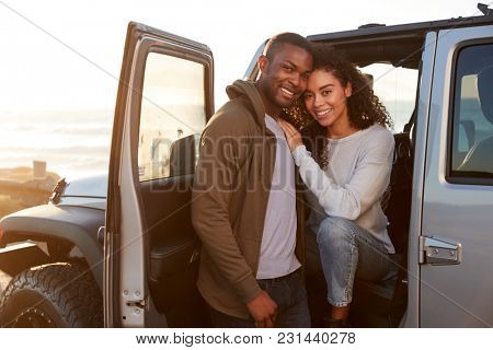 Young mixed race couple on a road trip embracing by car