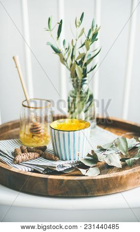 Healthy Vegan Turmeric Latte Or Golden Milk With Honey In Cup On Wooden Tray, Selective Focus