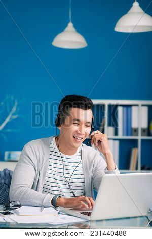 Happy Asian Businessman In Headset Talking To Client