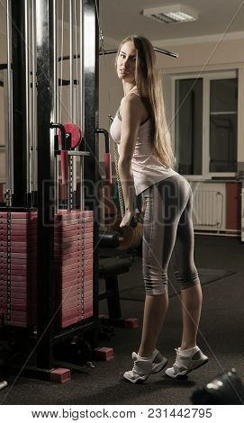 Young Business Woman Doing Exercise On A Fitness Machine In A Modern Fitness Center