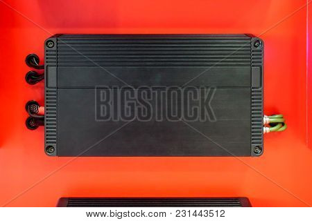 Car Audio Amplifier With Cables Isolated On Red Background