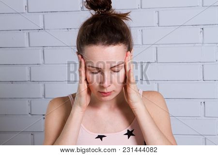 Woman With Headache Holding Her Hand To The Head. Brick Wall