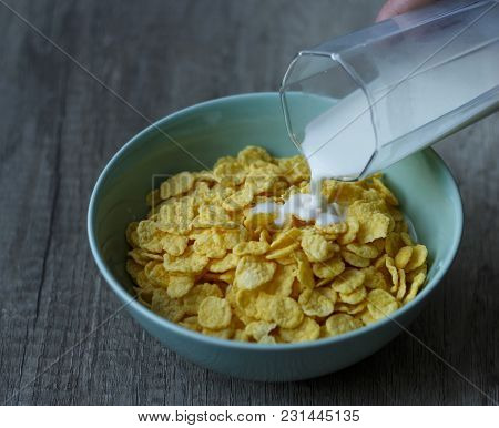 From A Glass Pour Milk In A Green Plate A Plate Of Flakes That Stands On A Wooden Table