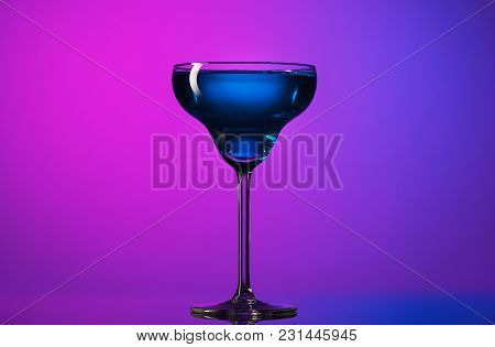 The Wine Stuffed Glasse With Cocktail Standing On The Table At Studio. Vivid Bright Colored Lighting
