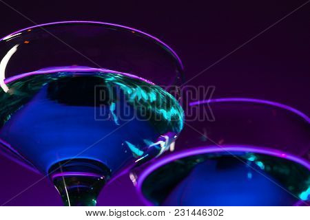 Two Wine Stuffed Glasses Standing On The Table At Studio. Vivid Bright Colored Lighting. Trendy In 2