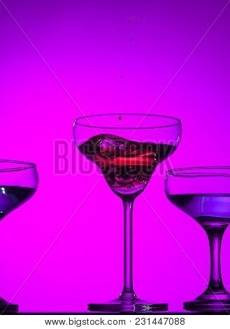 Three Wine Stuffed Glasses Standing On The Table At Studio. Vivid Bright Colored Lighting. Trendy In