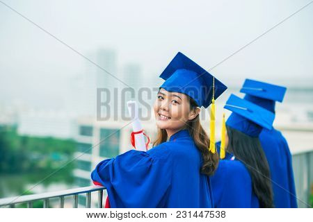 Cheerful Vietnamese Girl In Graduation Gowns And Her Friends