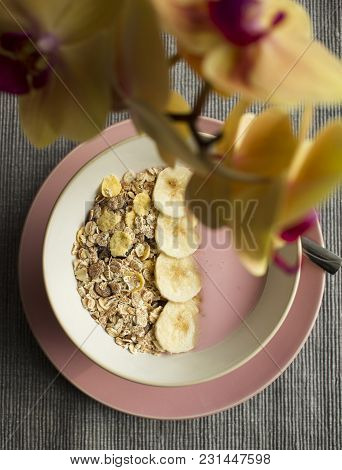Strawberry Yogurt With Cereals And A Banana In A Pink Plate