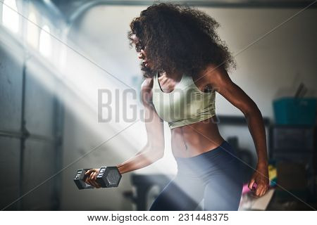 strong african american woman doing weight lifting at home inside garage