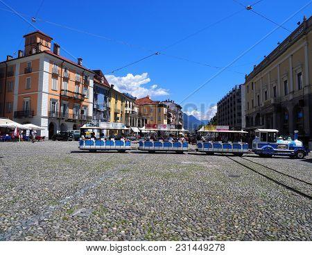 Locarno, Switzerland Europe On July 2017: Small Tourist Train, Colorful Buildings On Piazza Grande M