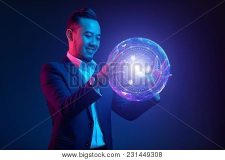 Smiling Vietnamese Businessman Holding Glowing Ball With Modern Interface
