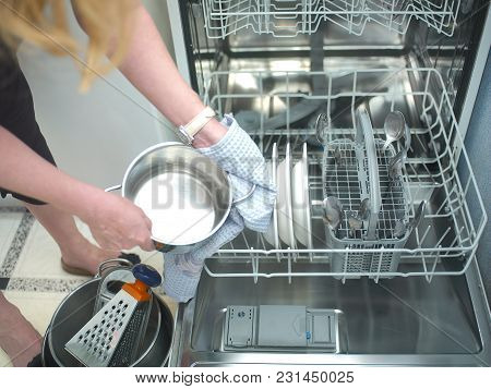 Woman Sorting Out Clean Dishware, A Dishwasher In The Background