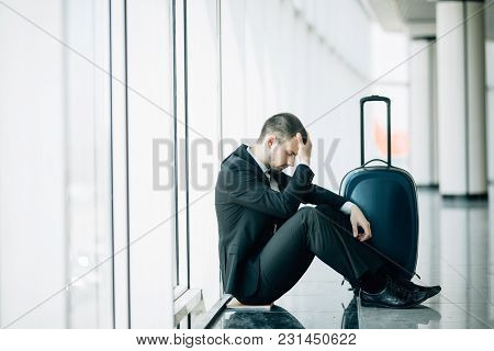 Business Man Sitting At The Terminal Airport On The Floor With Suitcase Flight Delay, Two Hands Touc