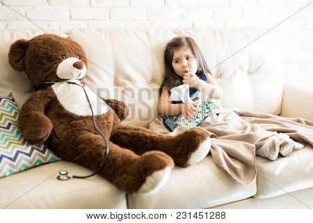 Cute Little Girl With Thermometer And Tissue Paper Sitting On Sofa With Doctor Teddy Bear With Steth