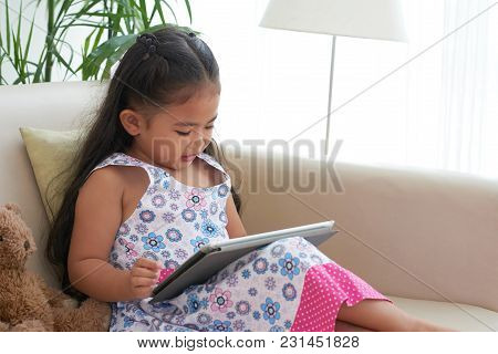 Little Girl Playing Game On Digital Tablet