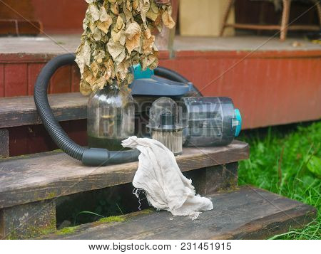 Withered Flowers In A Jar And A Vacuum Cleaner, Outdoor Shot, Concept Of A Housekeeping